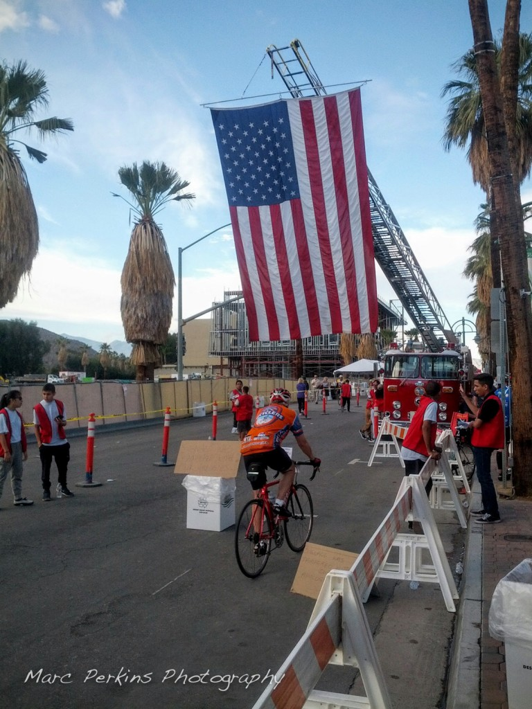 A giant flag hangs from a vintage fire truck at the finish line to the Tour de Palms 2016.
