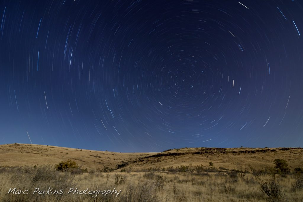 A long-exposure night image with moonlit illuminated hills and stars rotating around Polaris.
