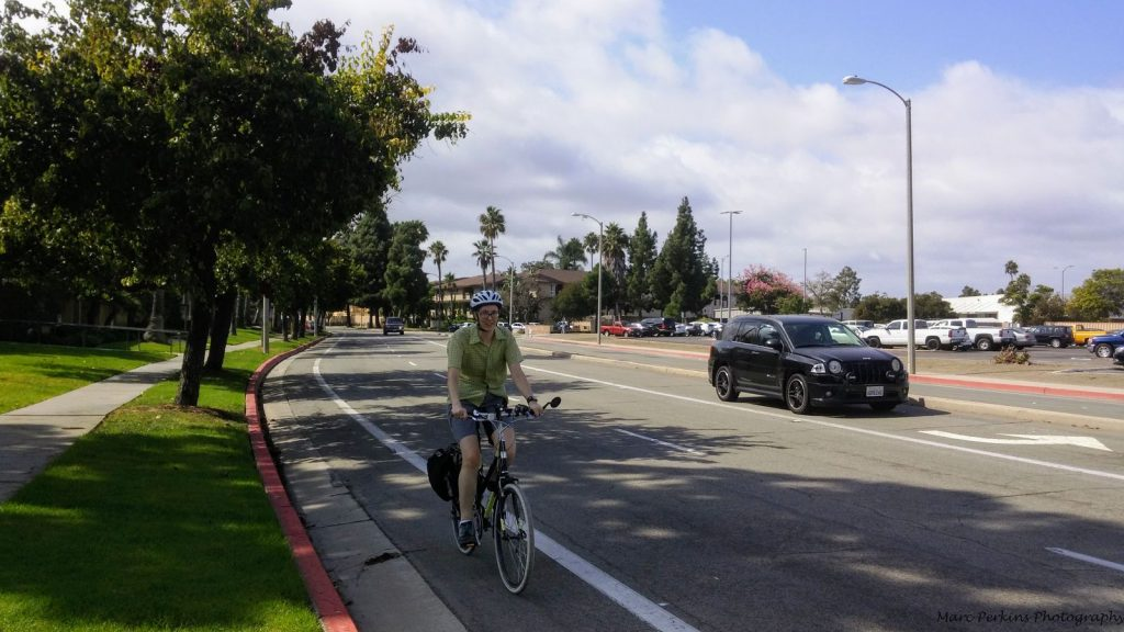 Cyclist in a bike lane with a car near her.