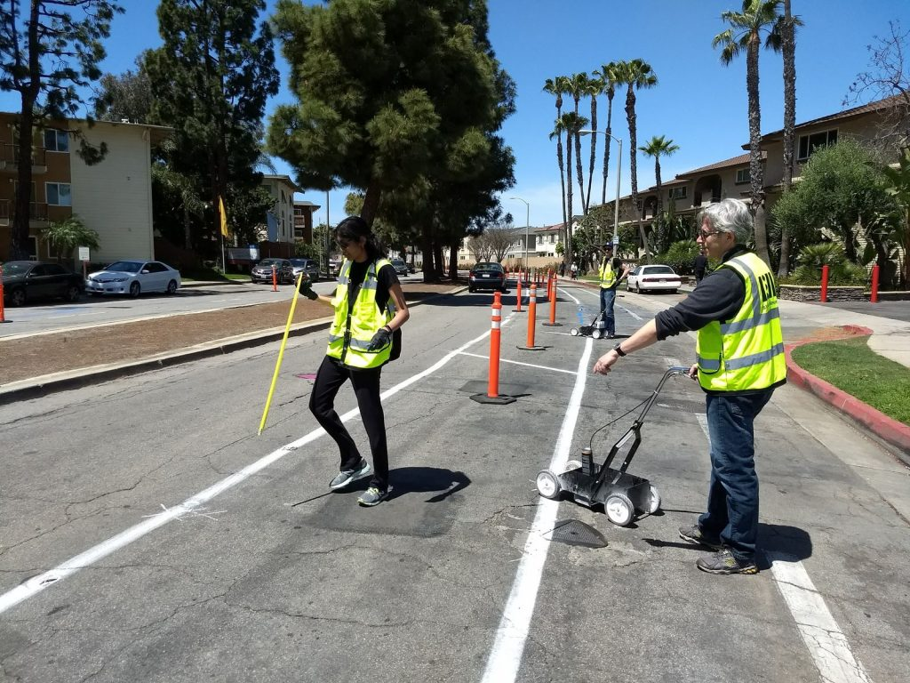 People install the demonstration protected bike lane along Merrimac Way in April 2018.