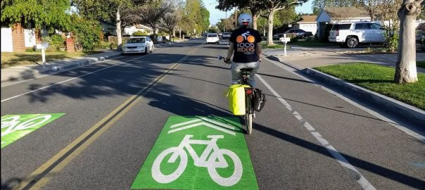 Person on bike in a street next to a Sharrow.