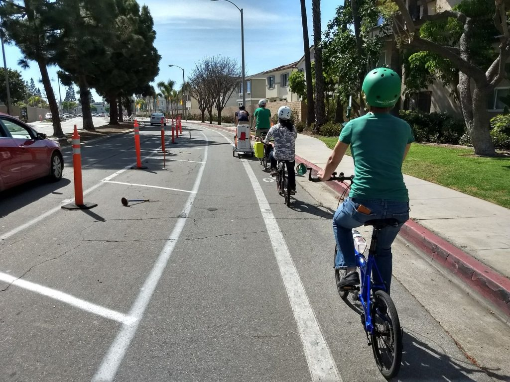 The OCC Food Riders travel down the demonstration protected bike lane on Merrimac Way.