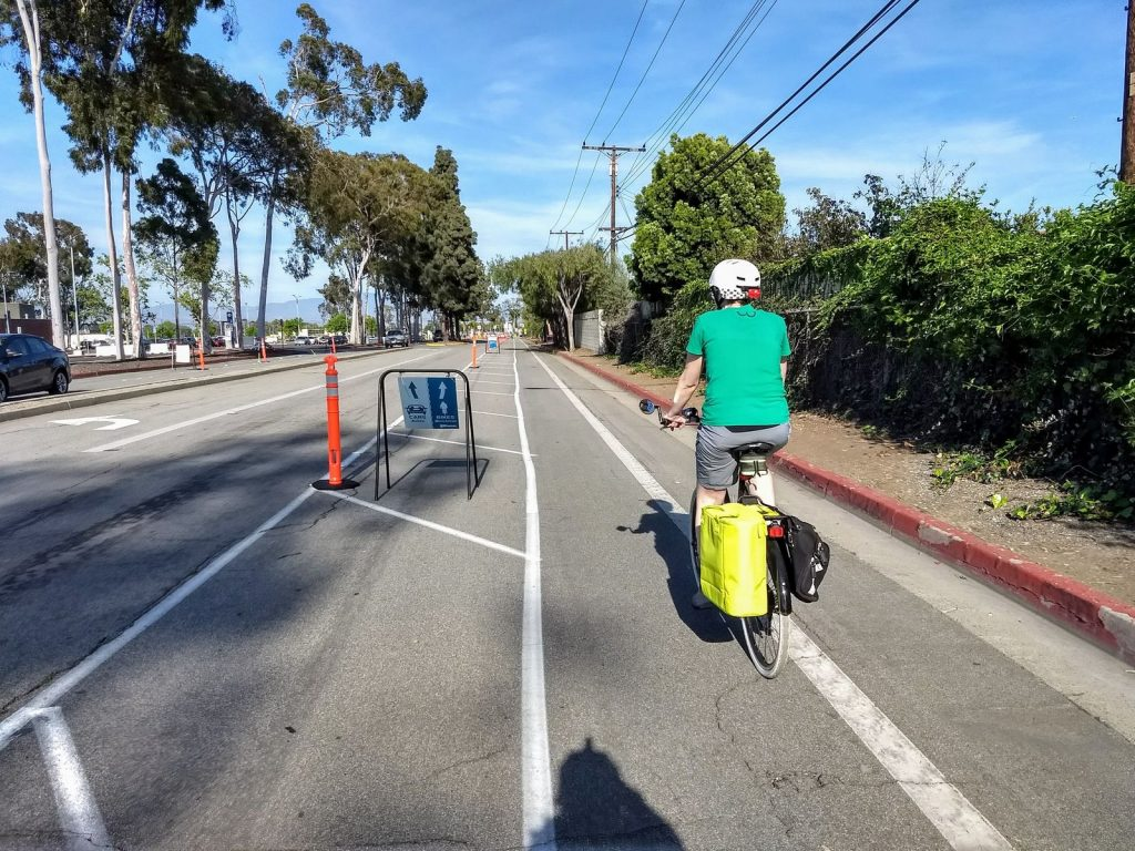 A bicyclist rides down the demonstration protected bike lane on Merrimac Way.