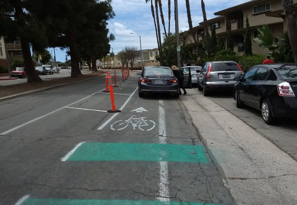 A car is parked in the demonstration protected bike lane along Merrimac Way.